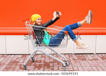 Fashion pretty cool young girl in trolley cart taking picture self portrait on smartphone wearing black jacket hat over colorful orange background