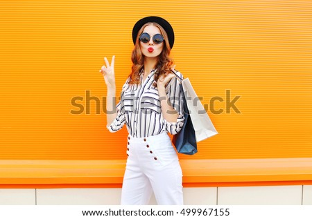 Fashion pretty cool young girl with shopping bags wearing a black hat white pants over colorful orange background