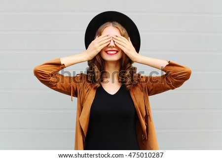 Stock Photo Fashion pretty cool young woman closes eyes cute smiling wearing a vintage elegant hat brown jacket playing having fun over grey background