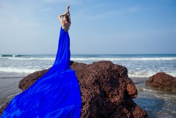fashion pretty female model posing on a beach with rocks in a long butterfly chameleon dress waterfall of skirt plume train.sensual perfume with a beautiful and young brunette woman wave tropical sand