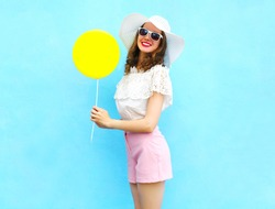 Fashion pretty smiling woman in straw hat with air balloon over colorful blue background