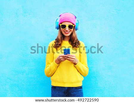 Fashion pretty sweet carefree woman listening music in headphones browsing smartphone wearing a colorful pink hat yellow sunglasses sweater over blue background