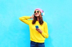 Fashion pretty sweet carefree woman listening to music in headphones with smartphone wearing a colorful pink hat yellow sunglasses sweater over blue background