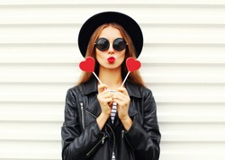 Fashion pretty sweet young woman with red lips making air kiss with lollipop heart wearing black hat leather jacket over white background