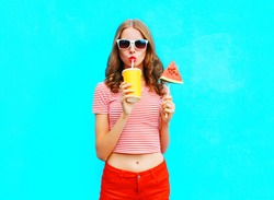 Fashion pretty woman drinks a fruit juice from cup holds slice of watermelon ice cream over a colorful blue background