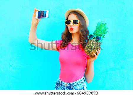 Fashion pretty woman taking picture self portrait on smartphone with pineapple wearing straw hat over colorful blue background