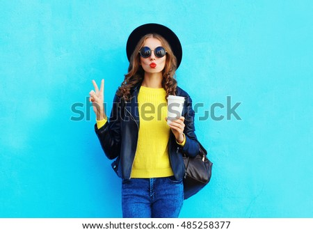 Fashion pretty woman with coffee cup wearing black rock style clothes over colorful blue background