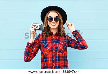 Fashion pretty young smiling woman and retro camera wearing a black hat, red checkered shirt over blue background