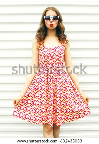Fashion pretty young woman wearing a dress over white background