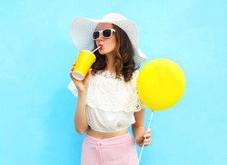 Fashion pretty young woman wearing a straw hat, sunglasses with air balloon drinks fruit juice from cup over colorful blue background