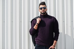 Fashion rich beard Arab man wear on turtle neck and sunglasses posed against green and white steel wall with jacket on hand. Stylish, succesful and fashionable arabian model guy.