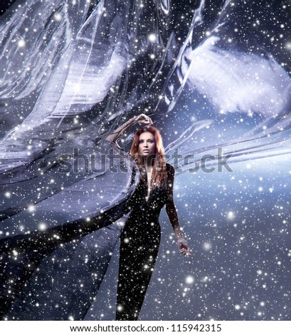 Fashion shoot of young attractive woman in blowing silk over the snowy background - stock photo