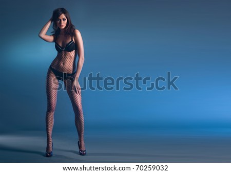 Fashion shoot of young sexy lady over smoke and darkness
