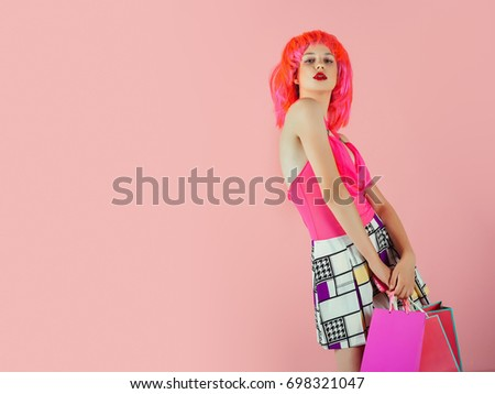 Fashion shopper posing on pink background. Sale and black friday. Holidays celebration concept. Woman with shopping bags. Girl wearing red wig and fashionable clothes, copy space #698321047