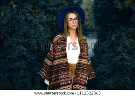 Fashion shot. Beautiful young woman in stylish clothes in the park. Ethnics, boho style.