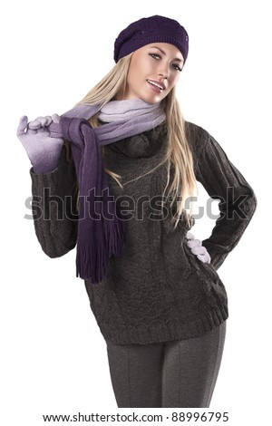 fashion shot of a beautiful blonde wearing a knitted cap, a scarf and gloves to grey sweater and pants