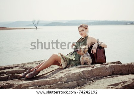 Fashion shot of a beautiful girl on the lake with a suitcase and a dog (Yorkshire terrier)