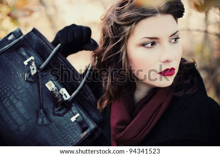 Fashion shot of a beautiful, professional model with a bag in her hands - stock photo