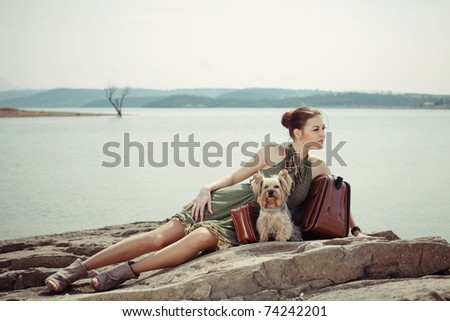 Fashion shot of a beautiful woman lying on the shore of the lake with a suitcase and a dog (Yorkshire terrier)