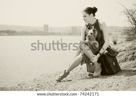 Fashion shot of a beautiful woman sitting on suitcase on the banks of the lake with the dog (Yorkshire terrier). In Black & White