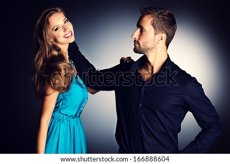 Fashion shot of a beautiful young couple posing at studio over dark background.