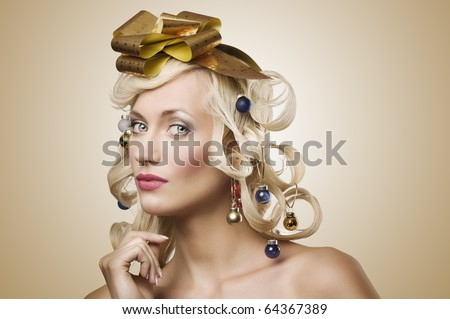fashion shot of a blond girl with curly hair stylish like a christmas tree with little noel decoration