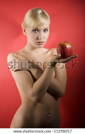 fashion shot of a glamour sensual girl keeping a red apple on red background