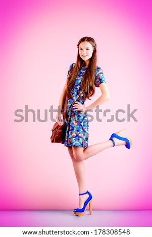 Fashion shot of a modern girl posing over pink background. Full length portrait. - stock photo