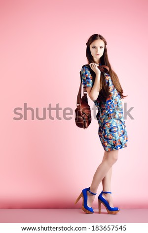 Fashion shot of a modern girl posing over pink background. Full length portrait.