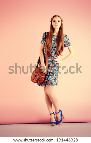 Fashion shot of a modern girl posing over pink background Full length portrait
