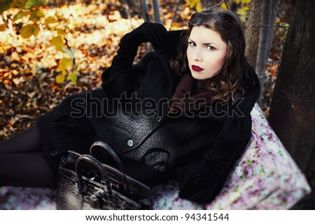 Fashion shot of a professional model lying on the yellow leaves and a gift box with flowers