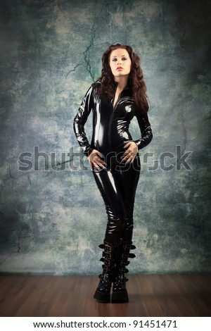 Fashion shot of a woman in black glossy overall and platform boots.