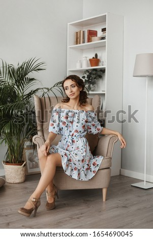 Fashion shot of a young beautiful woman in a short dress sitting in armchair. Portrait of a model girl with curly hair and slim body in light spring dress in the interior. Spring fashion. Summertime