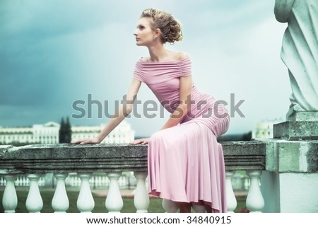 fashion shot of a young woman sitting near the sculpture in old mansion