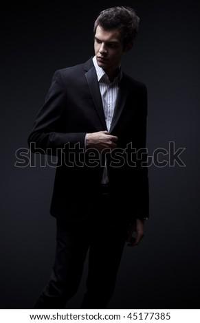 fashion shot of an elegant young man wearing suit