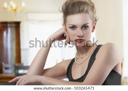 fashion shot of blond cute lady elegant red dress and pearl jewellery