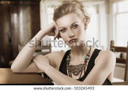fashion shot of blond cute woman in elegant black dress and necklace jewellery
