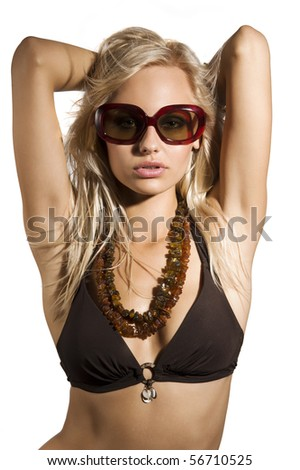 fashion shot of sexy blond girl with sunglasses in bikini taking pose