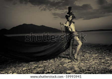 Fashion shot of the elegant young woman posing over beautiful landscape.