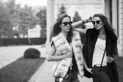 Fashion shot of two elegant beautiful girls in the sunset wearing sunglasses, fur vests . Two young women outdoor on the street. Shopping inspiration. Black and white concept