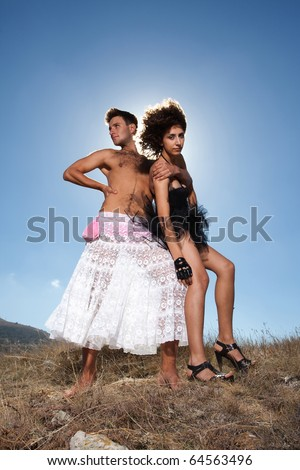 Fashion shot of unusual loving couple dressed in black and white; man embracing woman