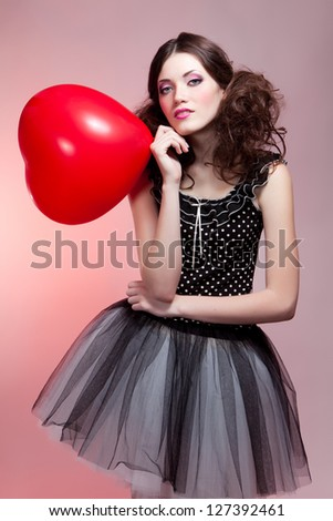 Fashion shot of woman in doll style with red balloon