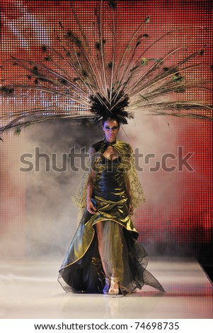 fashion show catwalk with beautiful young  woman in elegant and luxury dress with bird  peacock feather decoration