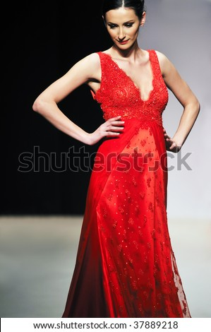 fashion show event and beautiful young woman at piste walking in luxury dress