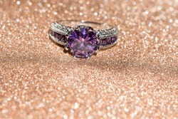 Fashion silver ring with purple amethyst on glittering background.