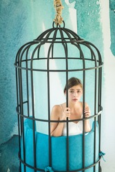 fashion slave in captivity of beauty. prisoner woman in cage - home confinement. freedom of cute girl in cage chair. modern furniture design and home comfort. justiceand crime. woman in iron cage.