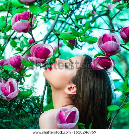 Fashion spring girl on Spring Magnolia flowers background. Woman on Spring blossom background