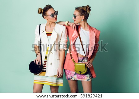 Fashion spring image of two girls, sisters  with horns hairstyle  posing in studio.Wearing stylish  casual jackets, striped pop dress , sunglasses.