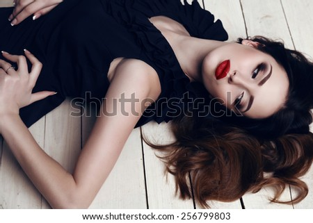 fashion studio photo of beautiful sensual woman with dark hair and bright makeup,