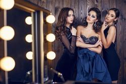 fashion studio photo of  beautiful sensual women with dark hair in luxurious dresses with bijou, posing in makeup room